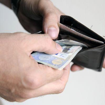 Mies ottaa euron seteleitä lompakosta.