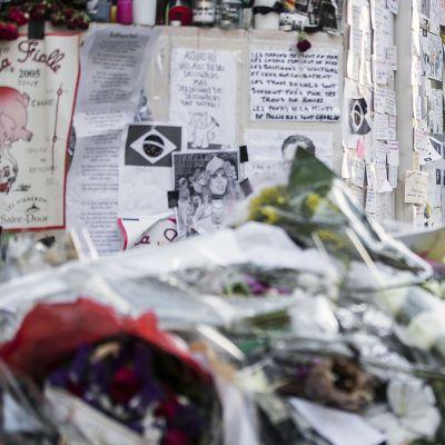 Mies kunnioittaa terrori-iskussa kuolleiden muistoa satiirilehti Charlie Hebdon toimituksen lähellä Pariisissa.
