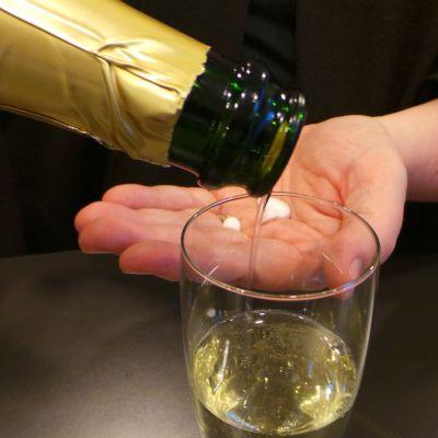 nainen kaataa pullosta kuohuviiniä, toisessa kädessä on lääkkeitä