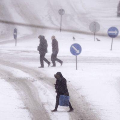 Ihmisiä likkeellä sankassa lumisateessa Helsingin keskustassa.