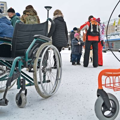 Tyhjä pyörätuoli jonka takana ihmisiä Kajaanin Raatihuoneentorilla.