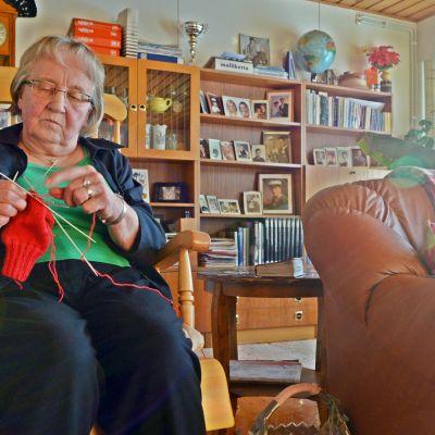 Saara Heikkinen istuu keinutuolissa ja neuloo.