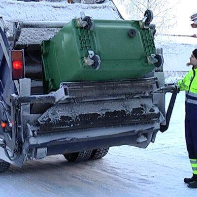 Jäteauton kuljettaja tyhjentää roska-astiaa.