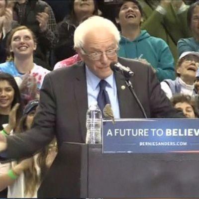 Pikkulintu istuu puhujanpöntöllä Bernie Sandersin edessä.