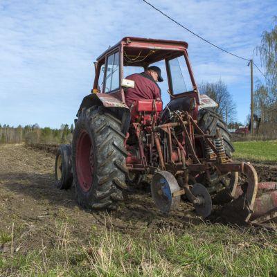 Traktori kääntää peltoa