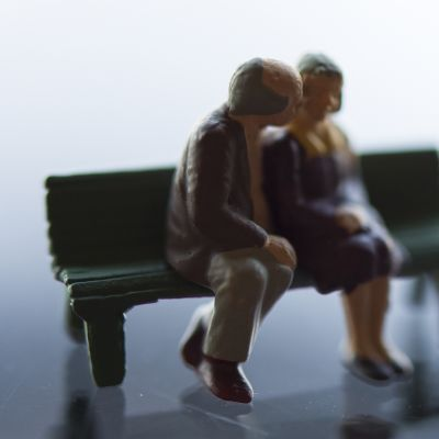 Kaksi miniatyyrihahmoa jotka esittävä vanhaa pariskuntaa puiston penkillä.