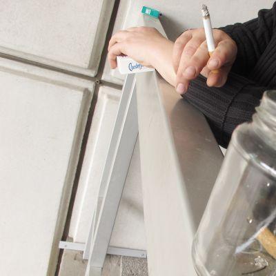 Nainen polttaa tupakkaa parvekkeella.