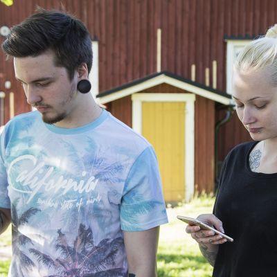 Pariskunta käyttää kännyköitään.