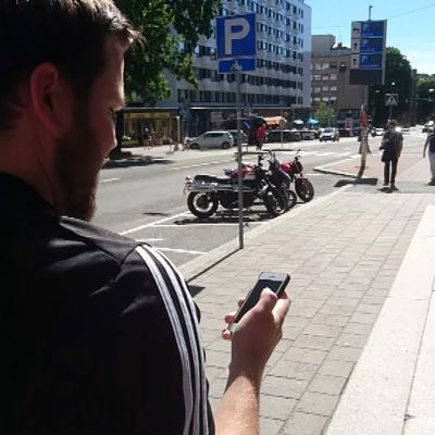 Mies kävelee ja katsoo puhelintaan.