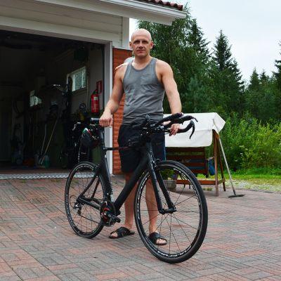 Roni Hooli pihassaan pyörän kanssa.