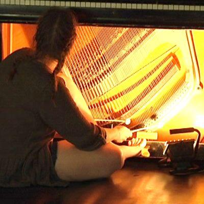 Nainen istuu pianon edessä, jonka sisukset on paljastettu. Hän soittaa pianoa pianon sisältä.