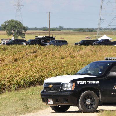 Poliisiauto ja runsaasti muita ajoneuvoja pellon laidalla.