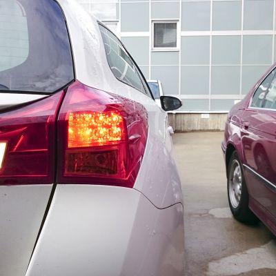 Auto peruuttaa parkkiruutuun.