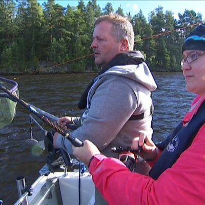 Timo Haavisto auttaa toimittaja Riina Mäentaustaa vetouistelussa - Riinan siiman päässä odottaa hauki.