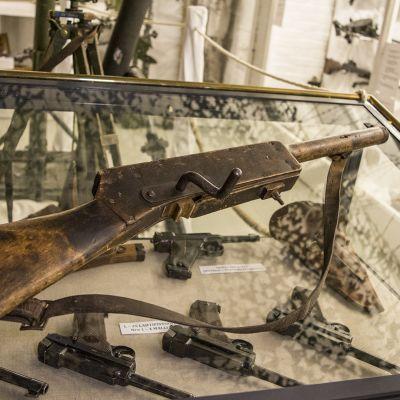 Suomi-harjoituskonepistooli vitriinin lasin päällää museossa