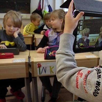 Oppilas ottaa iPadilla kuvaa luokkakavereistaan.