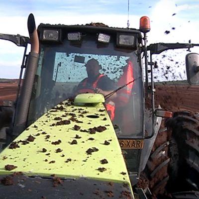 Iso traktori edestä kuvattuna turvekentällä