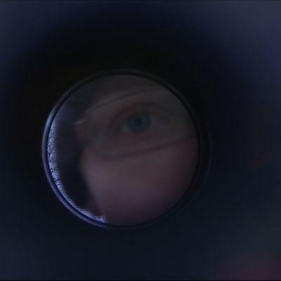Kim Kuntze katsoo kaukoputken läpi kameraan.