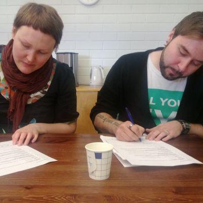 Ämy ry:n puheenjohtaja Päivi Lilja ja dokumentin ohjaaja Tuukka Tähti allekirjoittavat papereita
