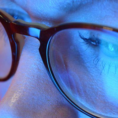 Naisen silmät, sininen valo heijastuu silmälaseista.