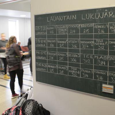 Koulun seinällä liitutaululle piirretty lukujärjestys.