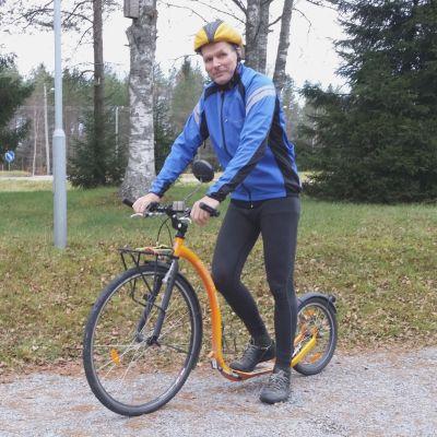 Juhani Olkkola keltaoranssin potkupyörän kanssa
