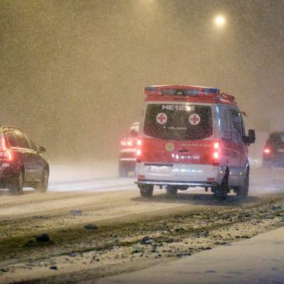 Ambulanssi ja autoja lumipyryssä