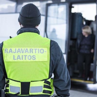 Rajavartija tarkkailee venäläisiä turisteja.