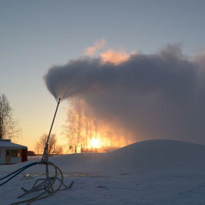 Lumilinnan lunta tehdään lumitykeillä joulukuussa 2016. Aurinko paistaa pöllyävän tykkilumen läpi.