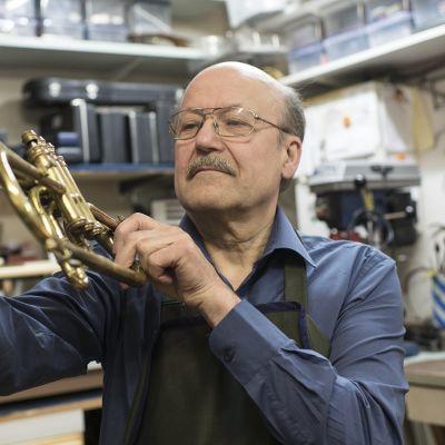 Pauli Ylitalo tarkastelee trumpettia.