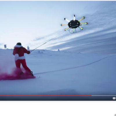 Kuvakaappaus youtube.com -sivustolta dronen eli lennokin avulla lautailevasta miehestä.