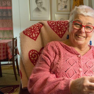Nainen neuloo ja hymyilee.