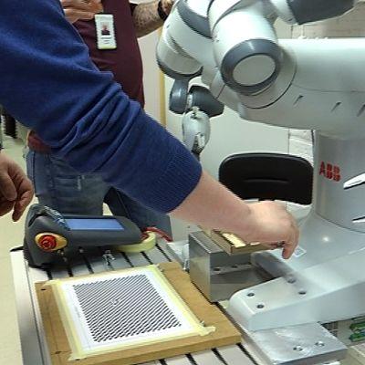 Ihminen tekee työtä yhdessä robotin kanssa.