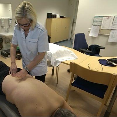 Fysioterapeutti Arja Pennanen tutkii potilasta.
