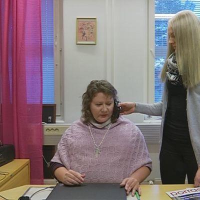 Henkilöhtainen avustaja Hanna Hammarström pitää puhelinta Marjo Luomasen korvalla puhelun ajan.