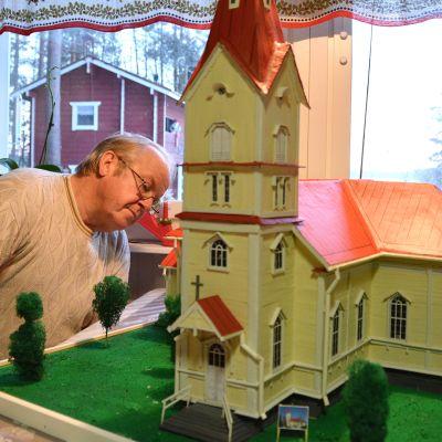 Kuvassa Heikki Känsäkangas kurkistaa tekemänsä Ylivieskan kirkon pienoismallin taa.