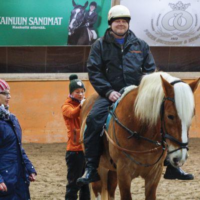 Ratsastusterapia-tutkimukseen osallistuva mies hevosen selässä. Kaksi naista seisoo hevosen vieressä.