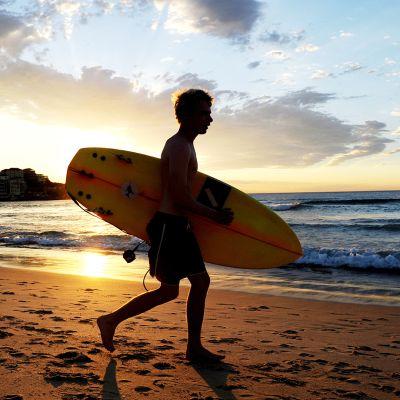 Nuori mies kantaa surffilautaa rannalla Sydneyssä.