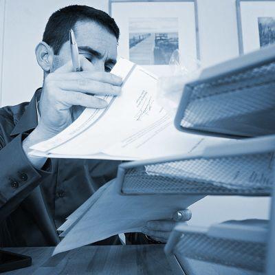 toimistotyöläinen selaa papereita