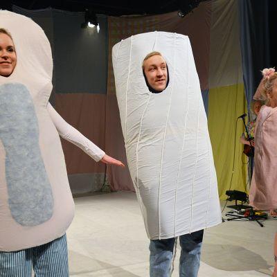 Menkkamusikaalin näyttelijöitä lavalla pukeutuneena siteeksi, tampooniksi ja kuukupiksi.