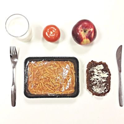 Einesruokalounas, spaghettia, leipä, omena ja tomaatti pöydällä.