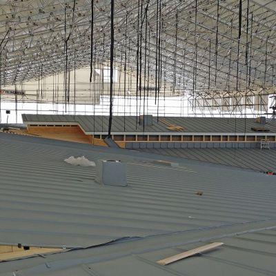 Kuvassa sääsuojan alla rakennettava kattotyömaa