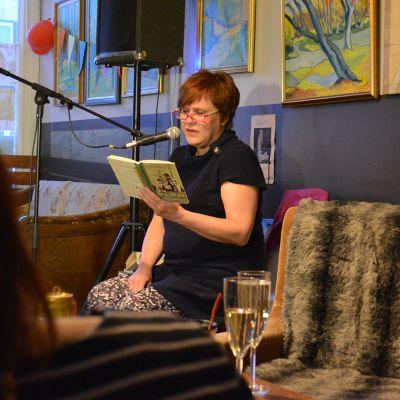 Nainen lukee ääneen satua pienessä baarissa.