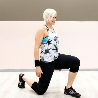 Personal trainer Anu Junnila tekee askelkyykkyä.