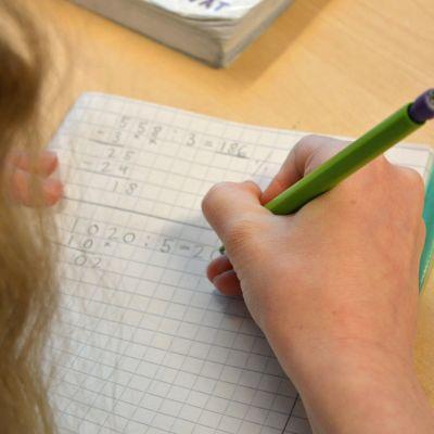 Tyttö laskee matematiikan tehtävää.