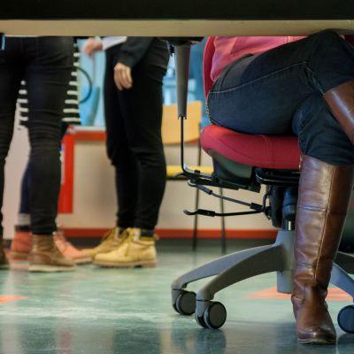 Naisen jalat ristissä työpöydän alla, taustalla  kolmen henkilön jalat.