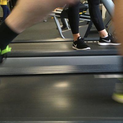 Mies juoksee juoksumatolla.