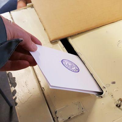 Äänestyslipuke tiputetaan uurnaan.