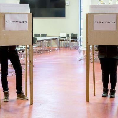 Ihmisiä äänestämässä äänestyskopissa.