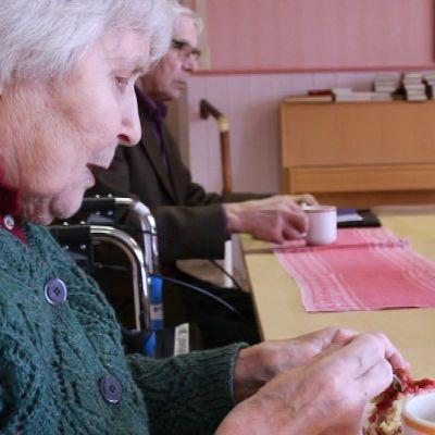 Vanha nainen syö piirakkaa pöydän ääressä